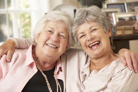 Portrait Of Two Retired Senior Female Friends Sitting On Sofa